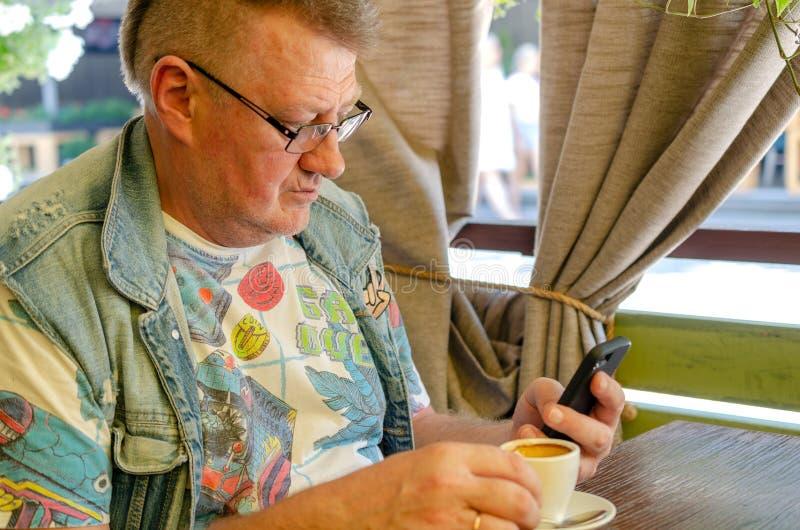 Portrait de l'homme supérieur bel, qui utilise son smartphone tandis que s image stock