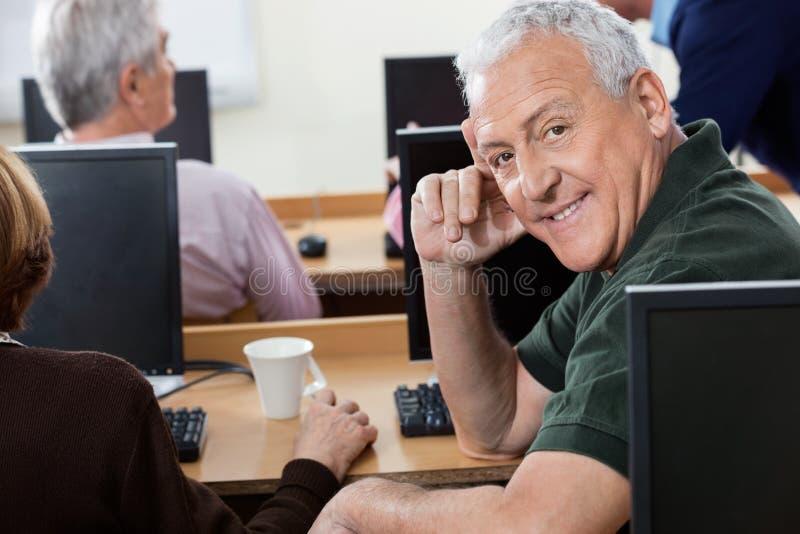Portrait de l'homme supérieur heureux s'asseyant dans la classe d'ordinateur image stock