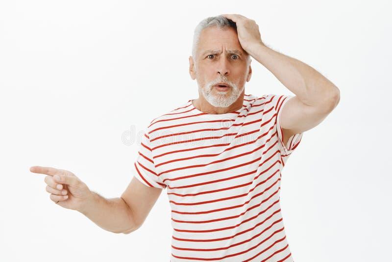 Portrait de l'homme supérieur intéressé et confus étant main se tenante préoccupée et remise en cause debout dupée sur la tête photo stock