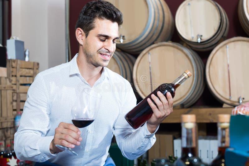 Portrait de l'homme tenant la bouteille et le verre de vin dans sec d'alcool image stock