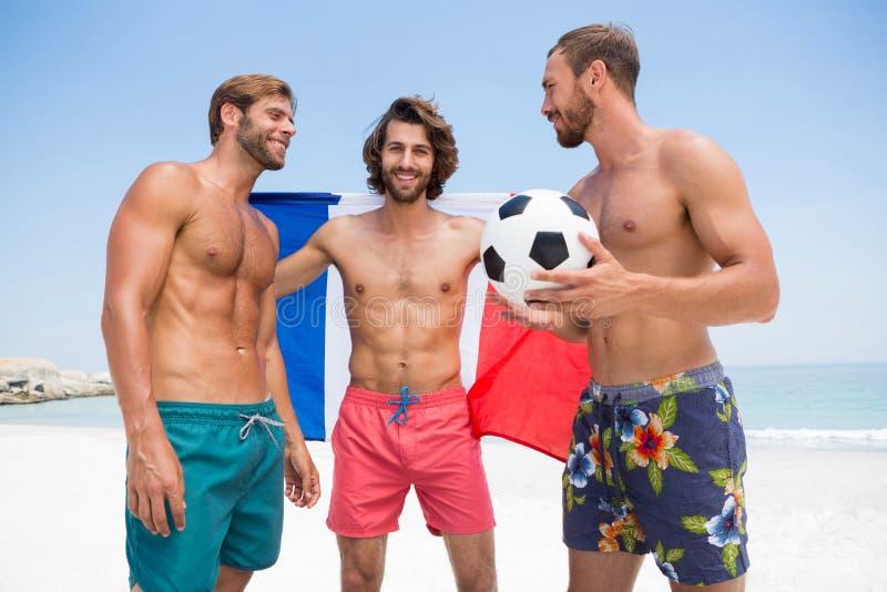 Portrait de l'homme tenant le drapeau français tout en se tenant avec les amis masculins à la plage images stock