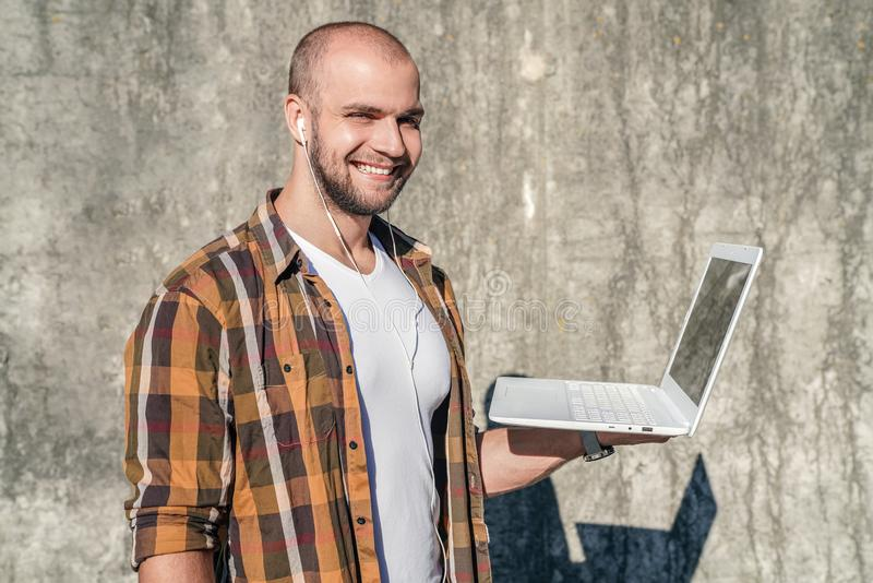 Portrait de l'indépendant barbu bel se tenant dehors contre le mur gris de grenier avec son ordinateur portable et moment de écou images libres de droits