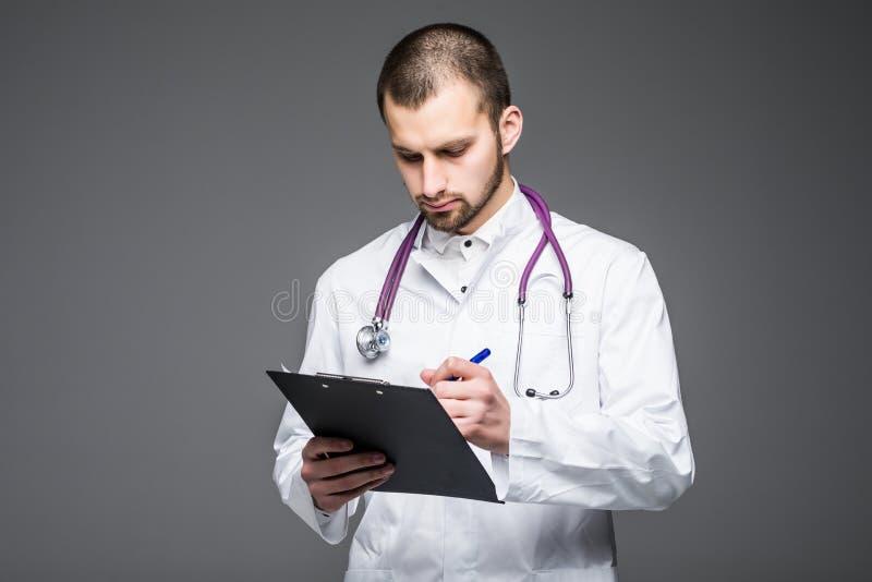 Portrait de l'interne de sourire barbu de médecin tenant le presse-papiers avec le papier vide Le Doc. porte les supports uniform photographie stock libre de droits