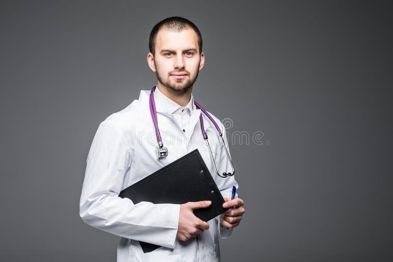 Portrait de l'interne de sourire barbu de médecin tenant le presse-papiers avec le papier vide Le Doc. porte les supports uniform photos stock