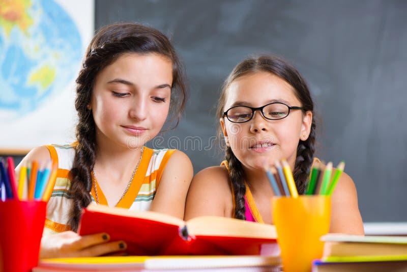 Portrait de la belle écolière deux dans la salle de classe photographie stock