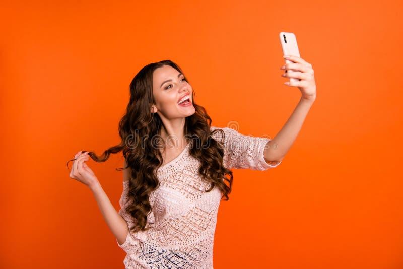 Portrait de la belle dame aux cheveux ondulés gaie gaie magnifique aimable de fille attirante jolie se tenant dans des mains photos libres de droits