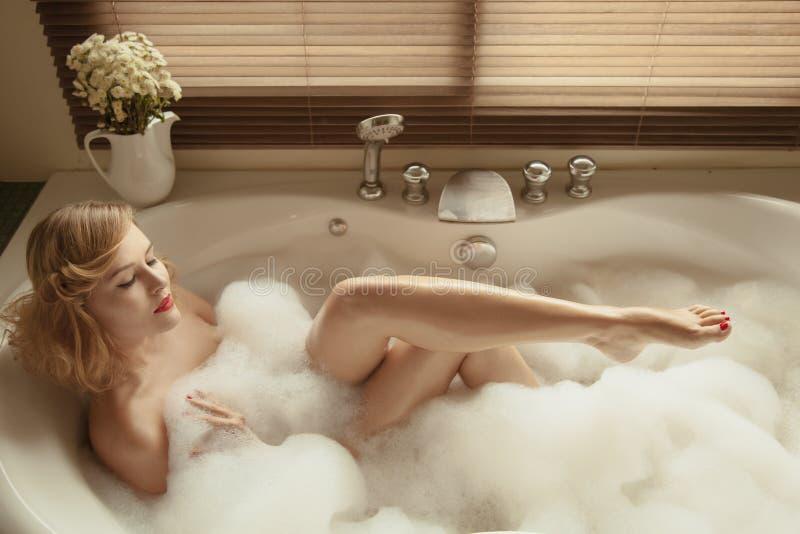 Belle femme élégante détendant dans un bain de station thermale image stock