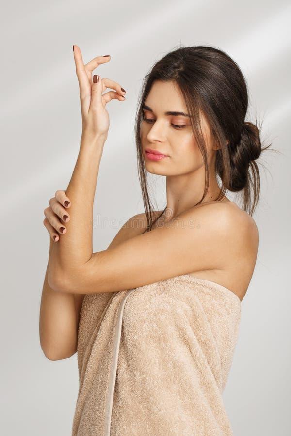 Portrait de la belle femme décontractée réparant ses mains avec de la crème après couverture de port de station thermale photographie stock libre de droits