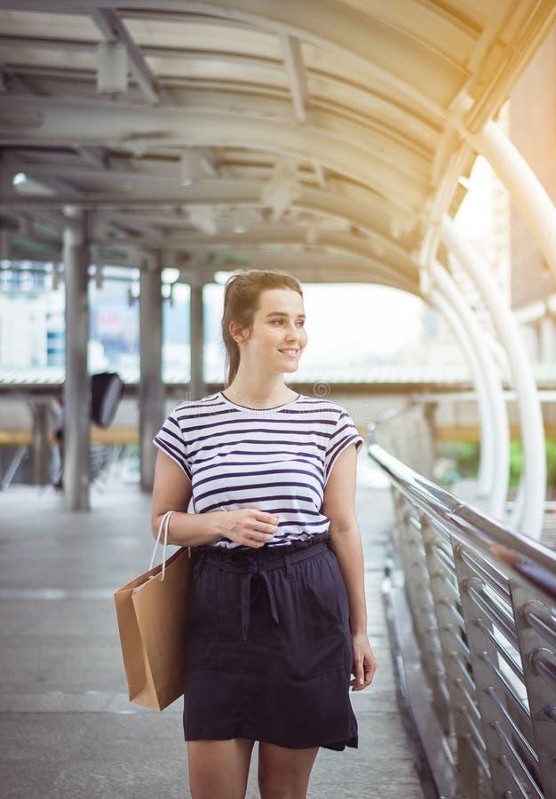 Portrait de la belle femme heureuse smling et tenant des sacs à provisions dans la ville, concept de mode de vie image stock