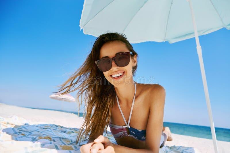 Portrait de la belle femme heureuse de sourire se bronzant dans des lunettes de soleil sur la plage sablonneuse à l'été Concept d image libre de droits
