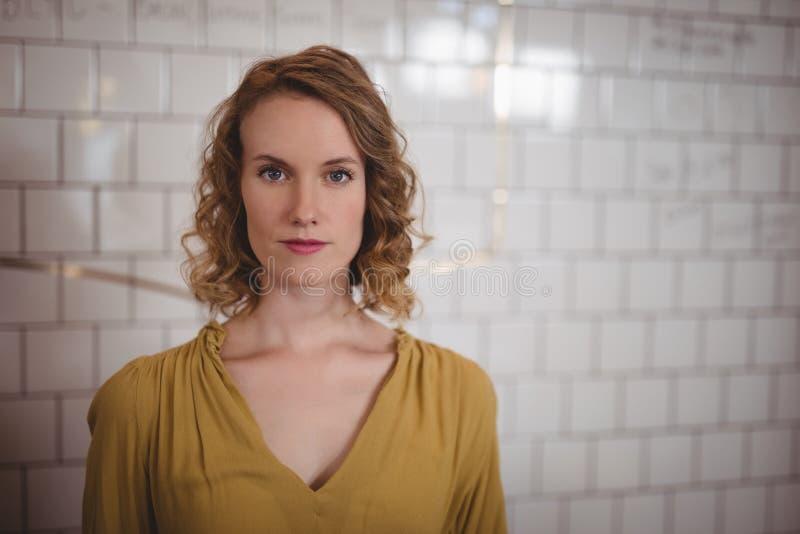 Portrait de la belle femme sûre se tenant contre le mur blanc photographie stock libre de droits