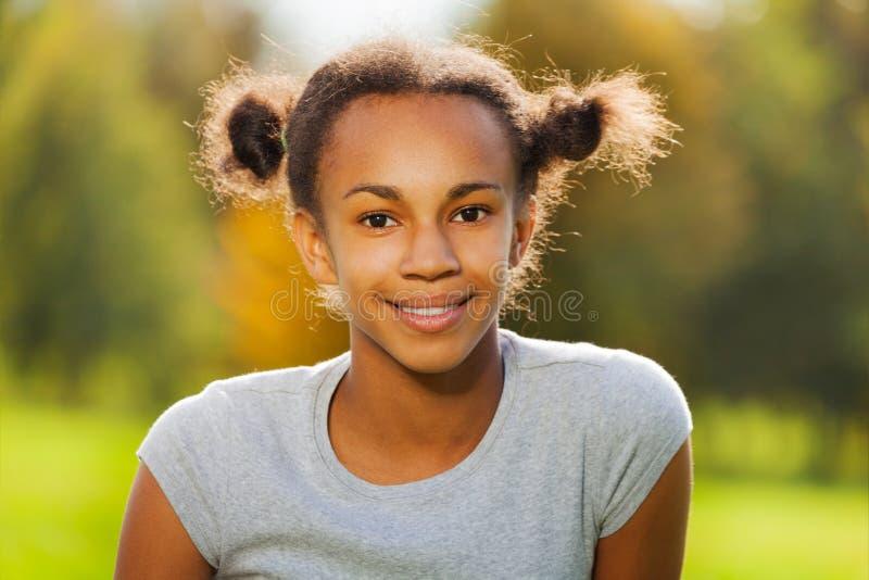 Portrait de la belle fille africaine s'asseyant en parc photos libres de droits