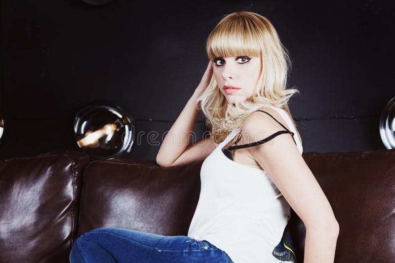 Portrait de la belle fille blonde s'asseyant sur le sofa image stock