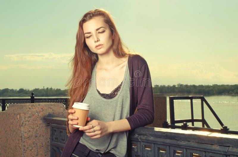 Portrait de la belle fille de l'adolescence d'une chevelure brune se tenant et regardant vers le bas Elle gardant la boisson à em photographie stock libre de droits