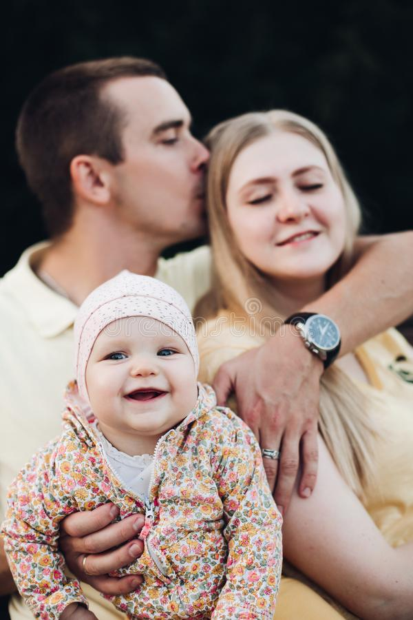 Portrait de la belle jeune famille s'asseyant ensemble dehors photos libres de droits