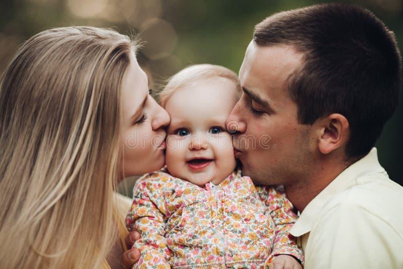 Portrait de la belle jeune famille s'asseyant ensemble dehors images libres de droits