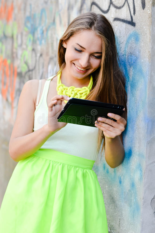 Portrait de la belle jeune femme blonde élégante à l'aide de l'ordinateur de PC de comprimé ayant le sourire heureux d'amusement images stock