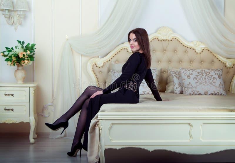 Portrait de la belle jeune femme de brune s'asseyant dans la chambre à coucher photos libres de droits