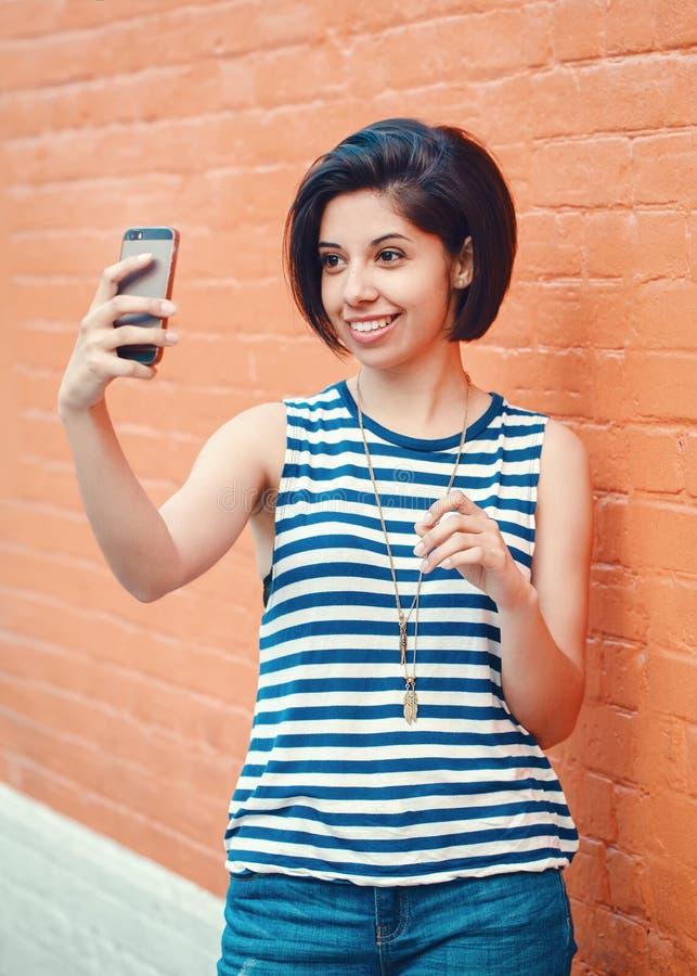 Portrait de la belle jeune femme hispanique latine de fille faisant la photo de selfie image stock