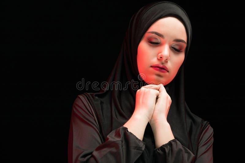Portrait de la belle jeune femme musulmane sérieuse portant le hijab noir avec les yeux fermés en tant que concept de prière sur  images stock