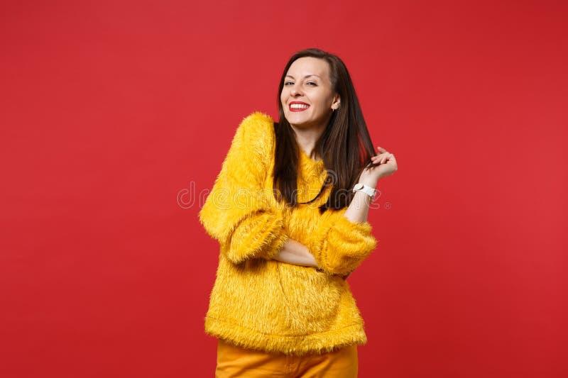 Portrait de la belle jeune femme renversante de sourire dans la position jaune de chandail de fourrure d'isolement sur le fond ro image stock