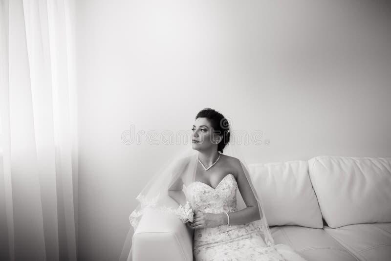 Portrait de la belle jeune mari?e heureuse s'asseyant sur le sofa photo libre de droits