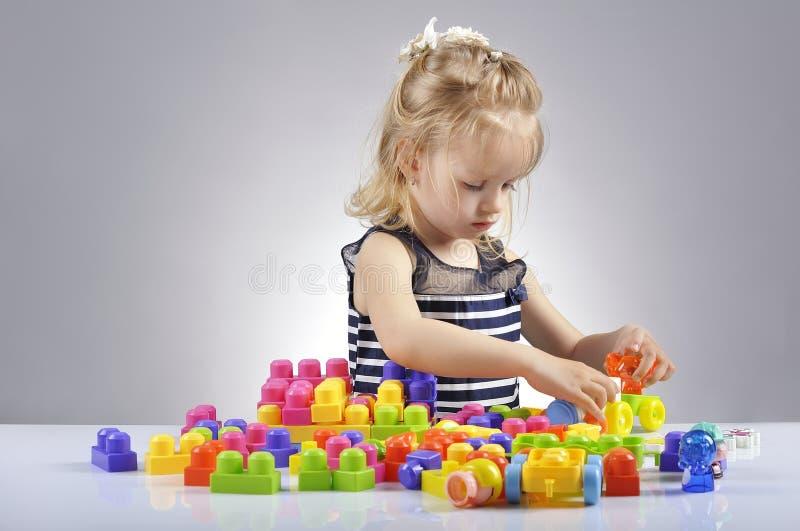 Portrait de la belle petite fille jouant avec les cubes en plastique en jouet photos libres de droits