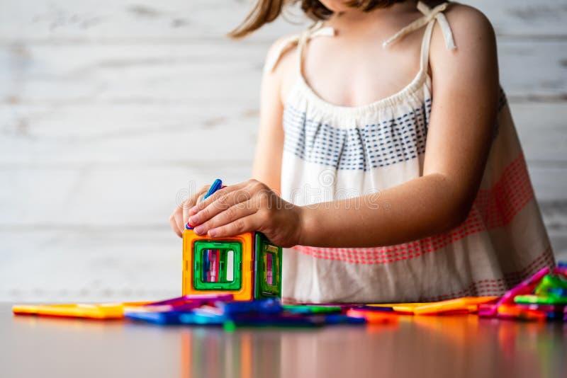 Portrait de la belle petite fille réfléchie jouant le kit en plastique de blocs d'aimant coloré, rêvassant et créant des idées d' photos libres de droits