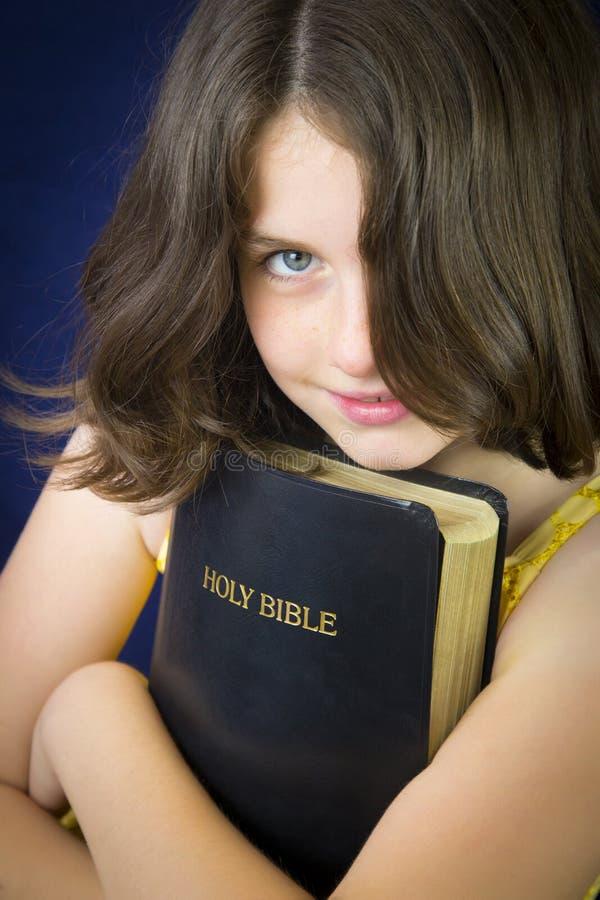 Portrait de la belle petite fille tenant la Sainte Bible photos libres de droits