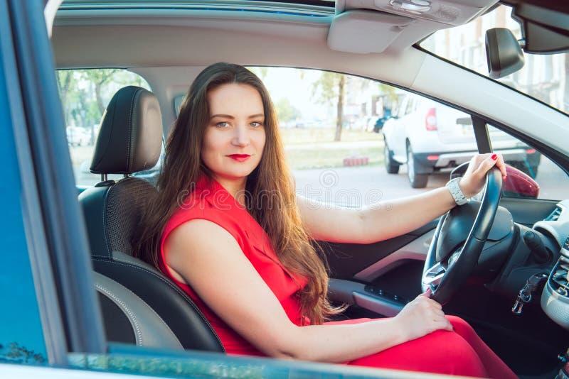 Portrait de la dame de sourire d'affaires, conducteur caucasien de jeune femme dans le costume rouge d'été regardant la caméra et photographie stock libre de droits
