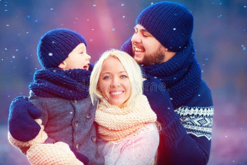 Portrait de la famille heureuse ayant l'amusement sous la neige d'hiver, saison des vacances photographie stock libre de droits