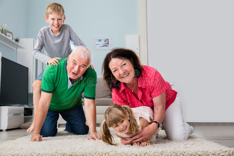 Portrait de la famille multi de génération se trouvant sur le tapis photographie stock libre de droits