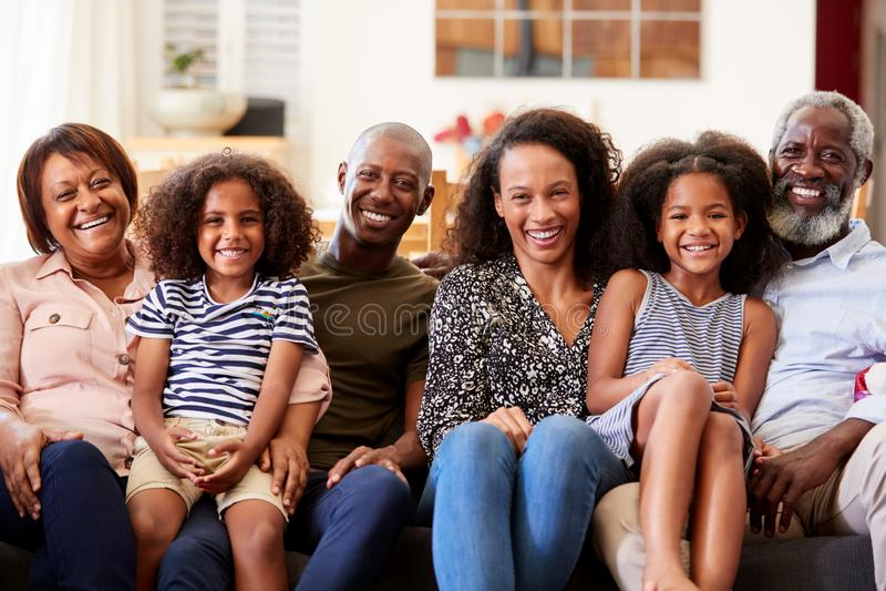 Portrait de la famille sur plusieurs générations de sourire s'asseyant sur Sofa At Home Relaxing Together images libres de droits