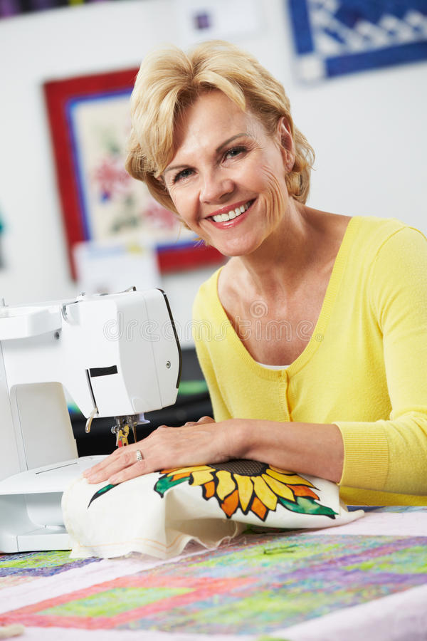 Portrait de la femme à l'aide de la machine à coudre électrique image stock