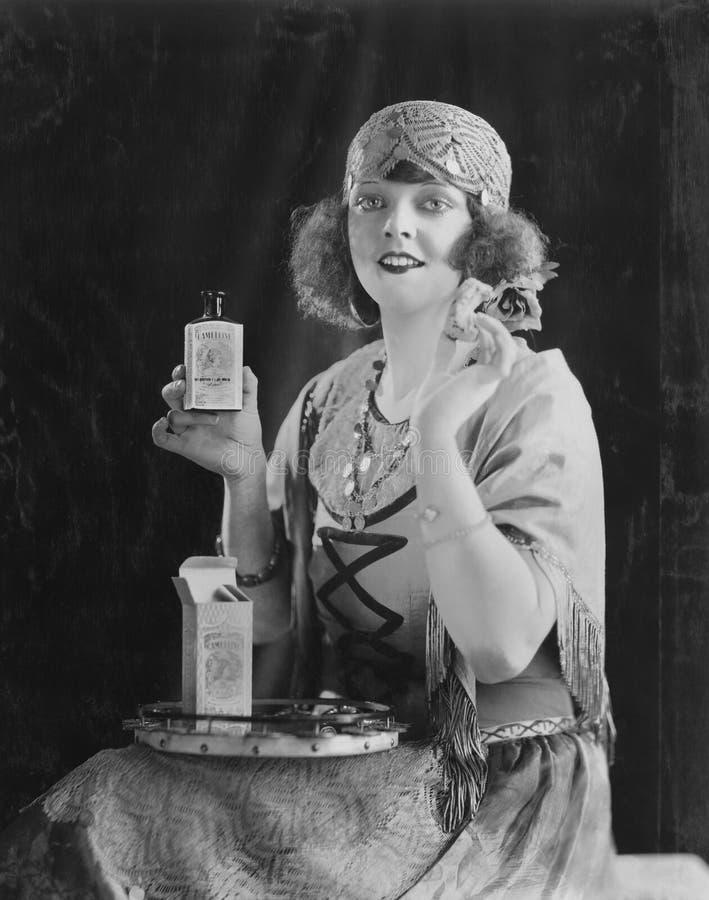 Portrait de la femme à l'aide du produit de beauté (toutes les personnes représentées ne sont pas plus long vivantes et aucun dom photos stock