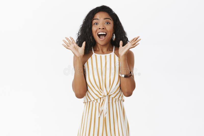 Portrait de la femme à la peau foncée enthousiaste joyeuse disant des nouvelles impressionnantes secouant les paumes augmentées d images stock