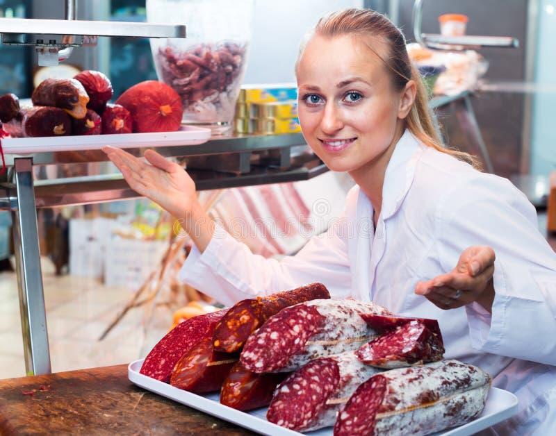 Portrait de la femme adulte ayant le plateau avec le salami photographie stock libre de droits