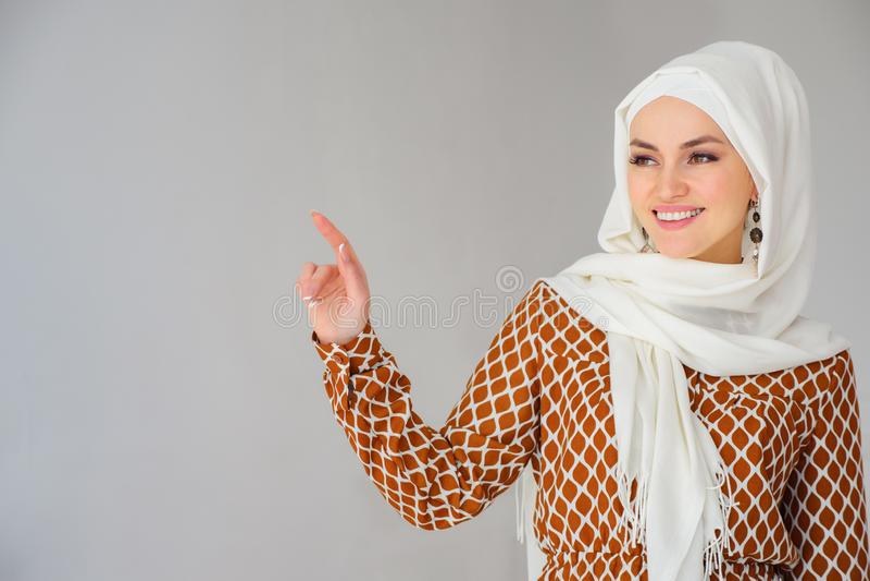 Portrait de la femme arabe magnifique dans le foulard dirigeant le doigt à l'espace de copie photo libre de droits