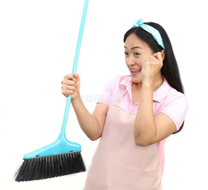 Portrait de la femme asiatique gaie ayant l'amusement tout en nettoyant d'isolement sur le blanc Balai heureux de participation d photographie stock