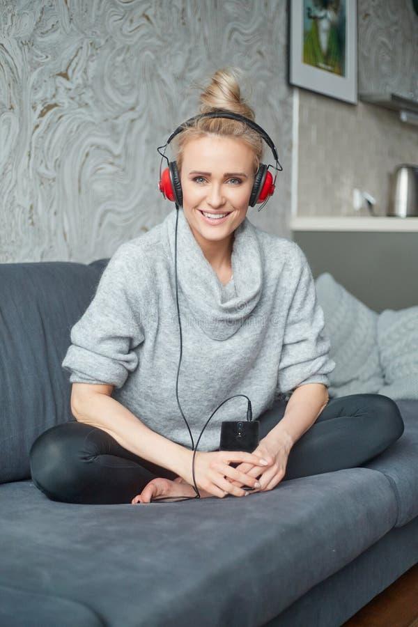 Portrait de la femme attirante à l'aide du téléphone intelligent pour écouter la musique photos libres de droits