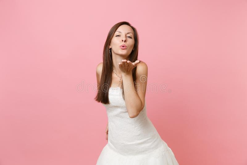 Portrait de la femme attirante de jeune mariée dans les lèvres de soufflement et l'envoi de dentelle de mariage de position blanc photo libre de droits