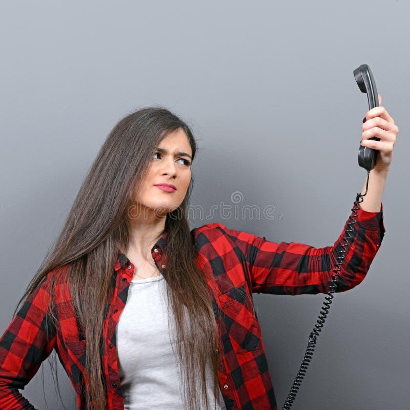 Portrait de la femme ayant l'appel téléphonique désagréable sur le fond gris images stock