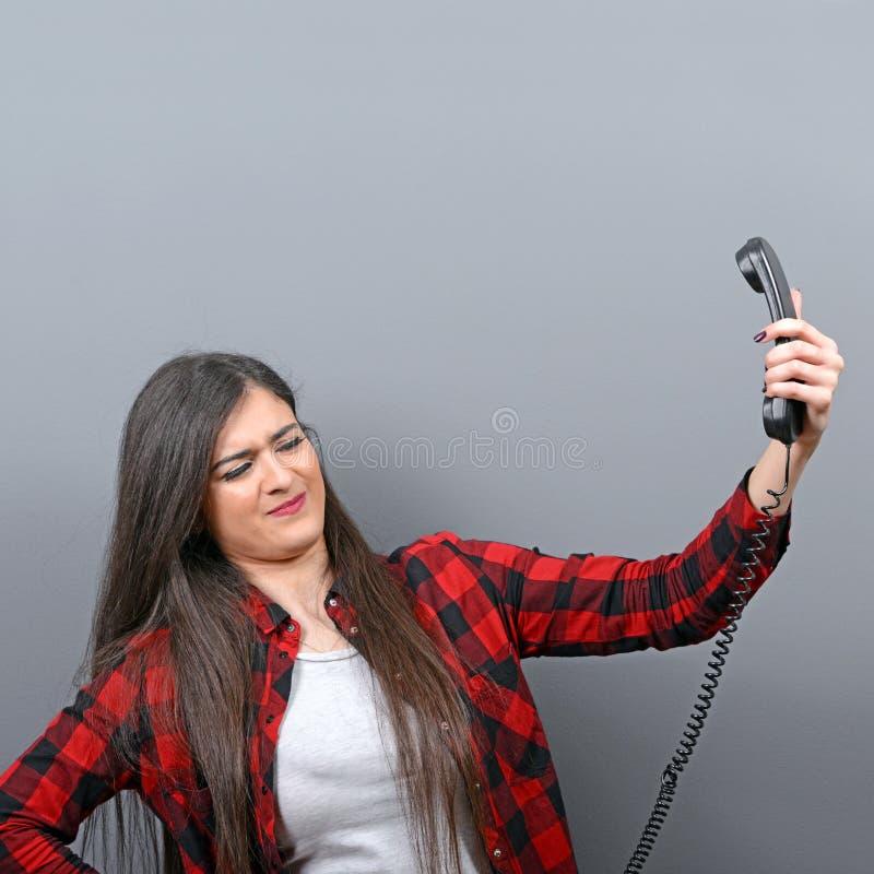 Portrait de la femme ayant l'appel téléphonique désagréable sur le fond gris photographie stock