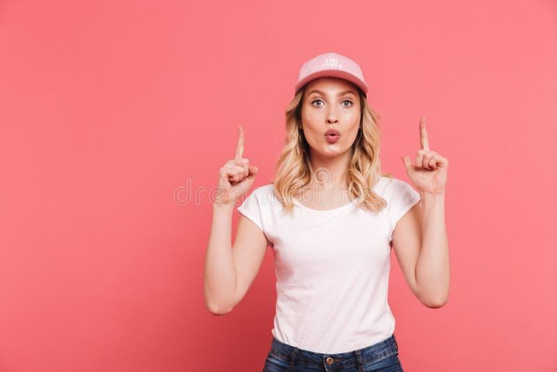 Portrait de la femme blonde ?l?gante 20s utilisant le T-shirt occasionnel et le chapeau dirigeant des doigts vers le haut au copy images stock