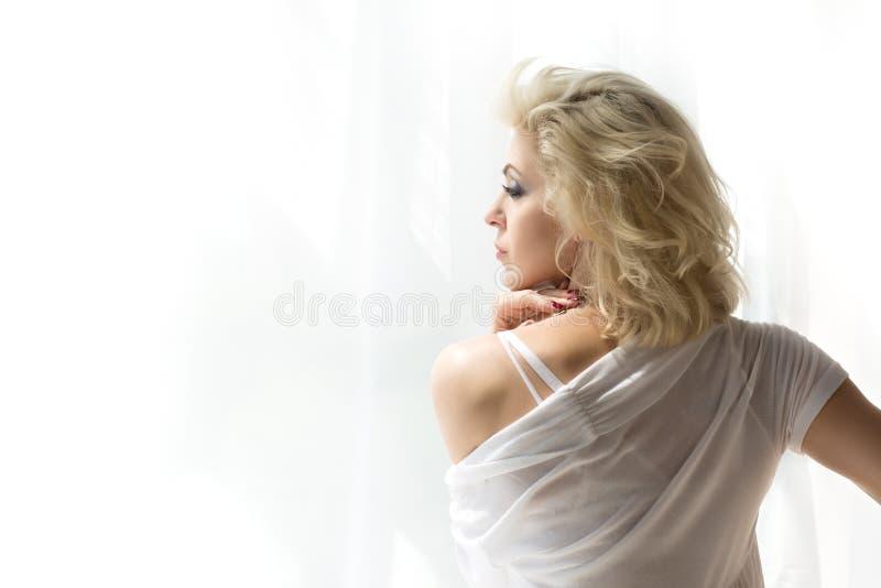 Portrait de la femme blonde adulte regardant la fenêtre images libres de droits