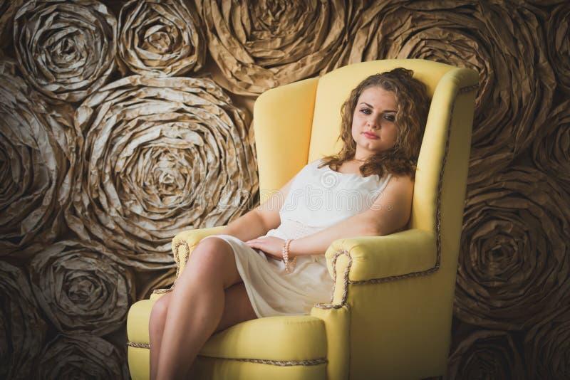 Portrait de la femme bouclée élégante s'asseyant dans le grand fauteuil photos stock