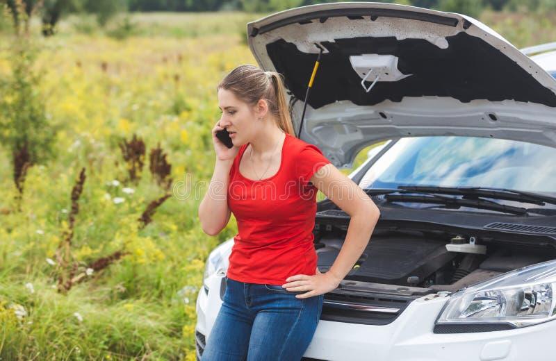 Portrait de la femme bouleversée de jeunes se penchant sur la voiture cassée dans le domaine et réclamant l'aide photos libres de droits