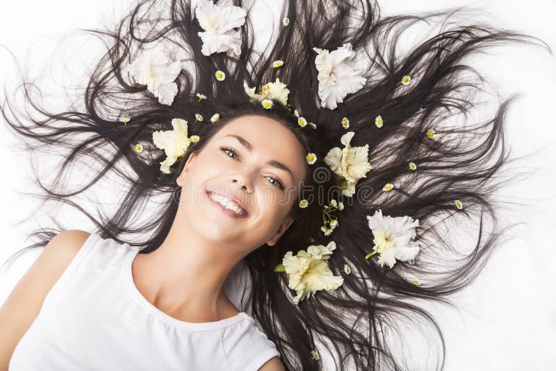 Portrait de la femme caucasienne de sourire heureuse de brune s'?tendant sur le plancher avec des cheveux ?cart?s images stock