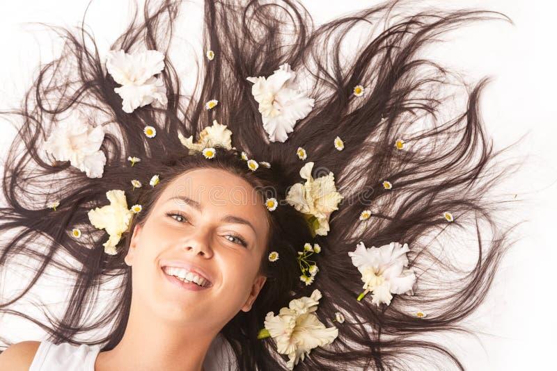 Portrait de la femme caucasienne de sourire heureuse de brune s'?tendant sur le plancher avec des cheveux ?cart?s photo stock