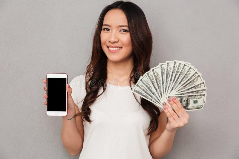 Portrait de la femme chanceuse asiatique 20s tenant la fan du Ba du dollar d'argent photos libres de droits